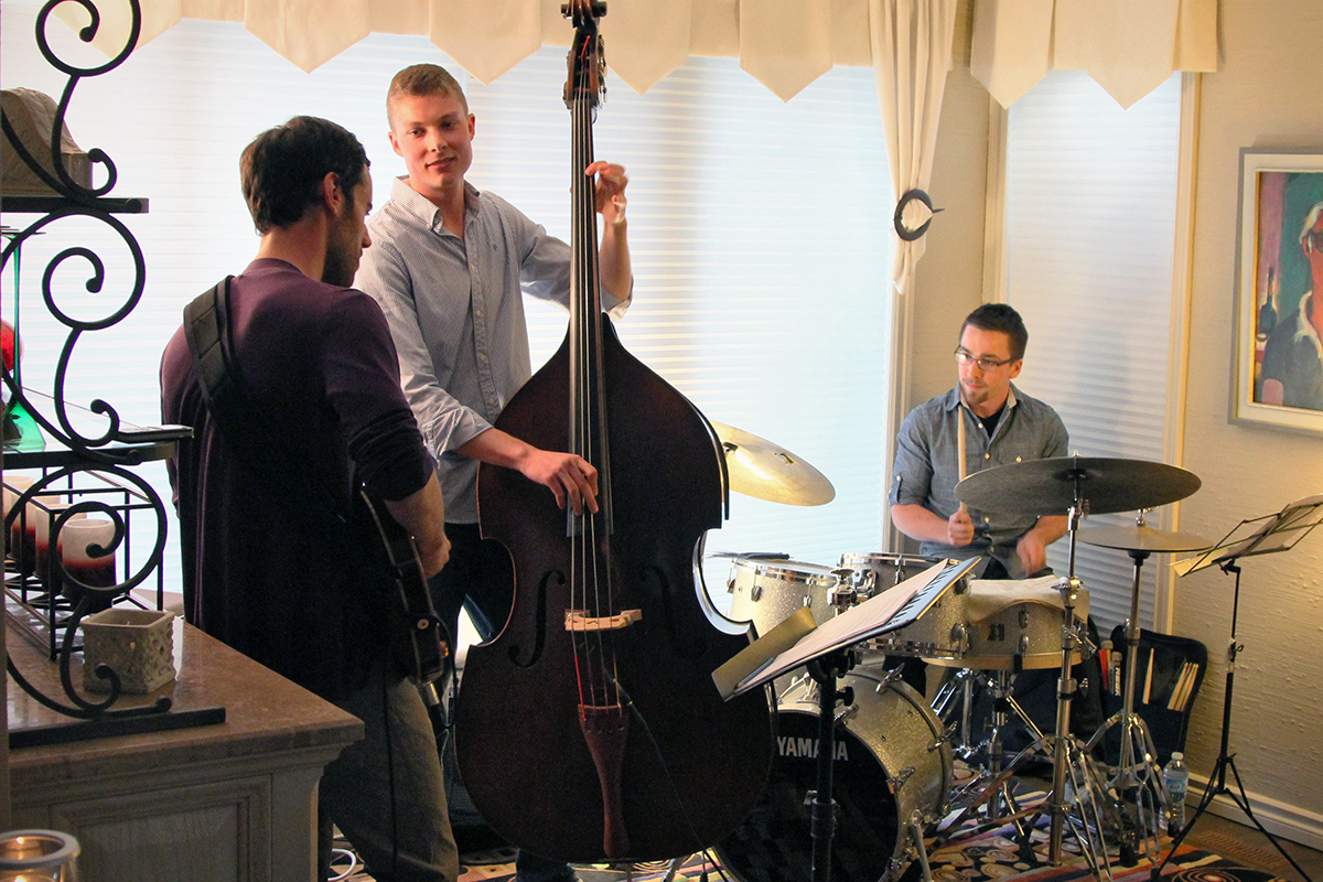 The Soren Nissen, Ian Wright and Nate Renner trio. The trio began playing as the last bit of sunlight was diffused into the living room. Photo taken Friday, May 17, 2013.